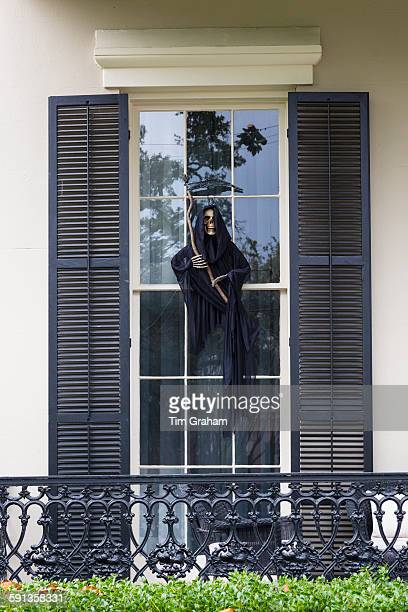 Scary Halloween voodoo grim reaper ghost character at mansion house with wrought iron in the Garden District of New Orleans USA