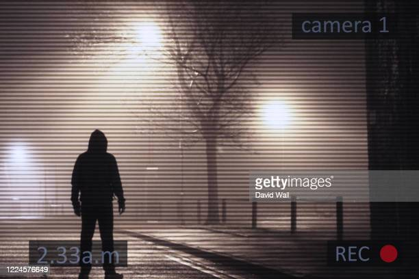 a scary hooded figure standing next to street lights on a foggy winters night. with a cctv surveillance edit. - crime stock pictures, royalty-free photos & images