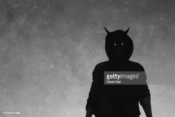 a scary, hooded horned figure with glowing evil eyes looking down to camera. with a grainy textured edit - devil stock pictures, royalty-free photos & images