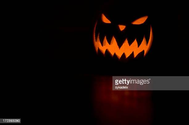 scary jack o lantern on orange on black background - scary pumpkin faces stock photos and pictures