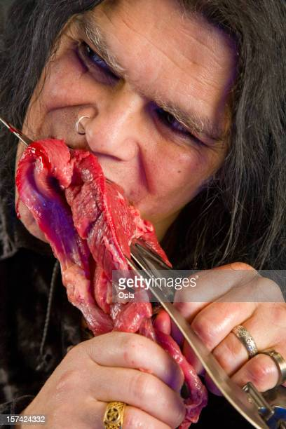 Scary man eating raw  meat