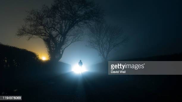a scary, mysterious hooded figure, standing in front of a bright light on a country lane, on a spooky foggy winters night. - paranormal stock pictures, royalty-free photos & images
