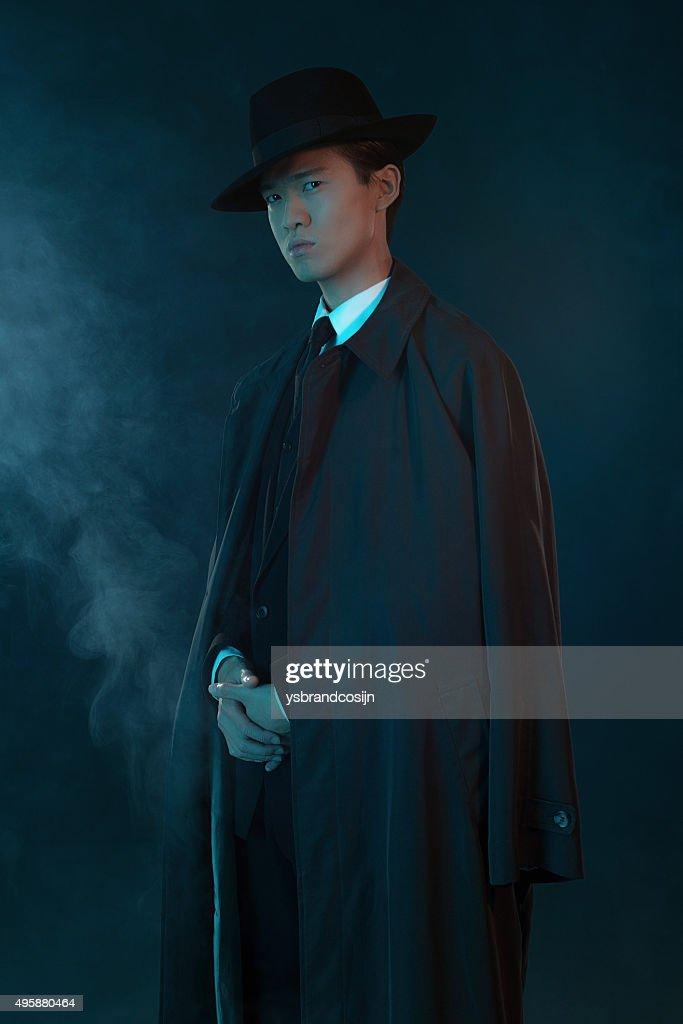 scary retro 1940 asian gangster fashion man wearing long coat stock