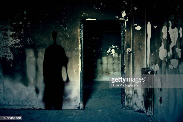 scary scene with spooky shadow in a dark room of an abandoned building - mord stock-fotos und bilder
