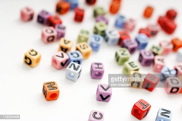 scattered cubed beads of alphabet letters against white - bead stock pictures, royalty-free photos & images