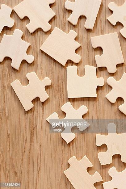 Scattered puzzle pieces on wood