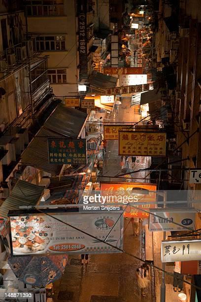 scattered shop and restaurant advertising in the evening. - merten snijders stockfoto's en -beelden