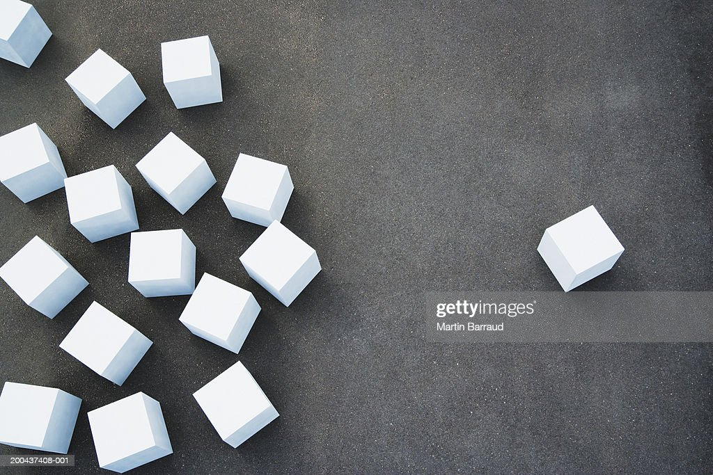 scattered white cubes on ground one cube set apart from others