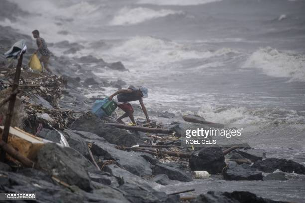 TOPSHOT A scavenger collects recyclable materials along the breakwater amid strong waves as weather patterns from Typhoon Yutu affect Manila Bay on...