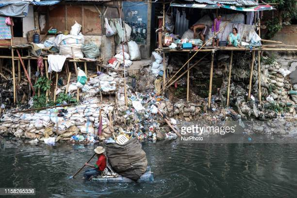 A scavenger wades through a river using a makeshift raft to collect reusable items at a slum area in Jakarta Indonesia July 28 2019
