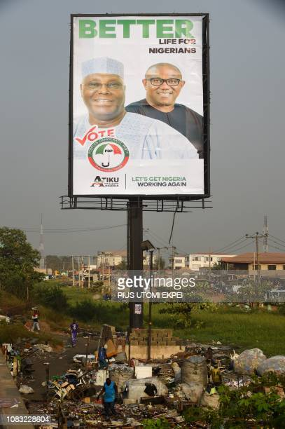 Scavengers collect recyclable materials under a campaign billboard of presidential candidate from the opposition People's Democratic Party Atiku...