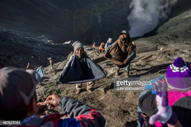 Scavengers stand on the inner wall of Mount Bromo volcano to catch offerings by members of the Tenggerese tribes in Probolinggo town located in...