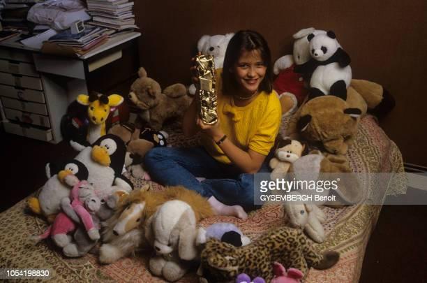 Sceaux France mars 1983 Sophie MARCEAU 16 ans chez ses parents souriante assise sur son lit au milieu des peluches posant avec le César du meilleur...