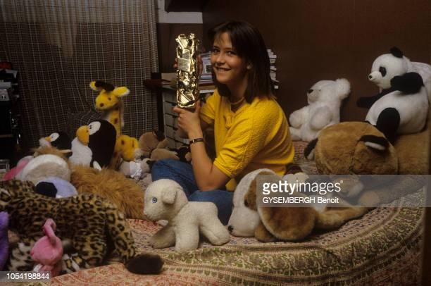 Sophie MARCEAU 16 ans chez ses parents souriante assise sur son lit au milieu des peluches posant avec le César du meilleur jeune espoir féminin 1983...