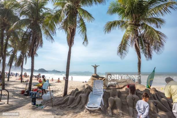 scene at copacana beach on sunday with sculpture made of sand