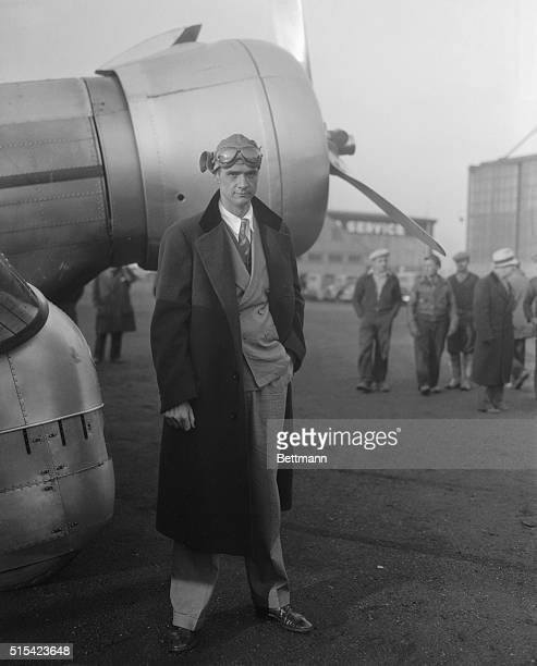 Scene at Newark Airport as crowd of spectators swarm about the plane of Howard Hughes millionaire motion picture producer after Hughes has completed...