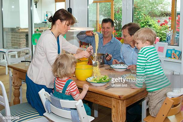 Scene family: father, mother and two children having lunch in the dining room. The grandfather is visiting and there's Spaghetti with fresh salad....