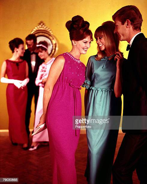 1964 A scene from an evening party where two groups a people chat to each other Both sets of models are wearing smart evening dress