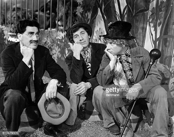 Scene from an unidentified Marx Brothers film showing Groucho Chico and Harpo sitting down on buckets resting their fists under their chins