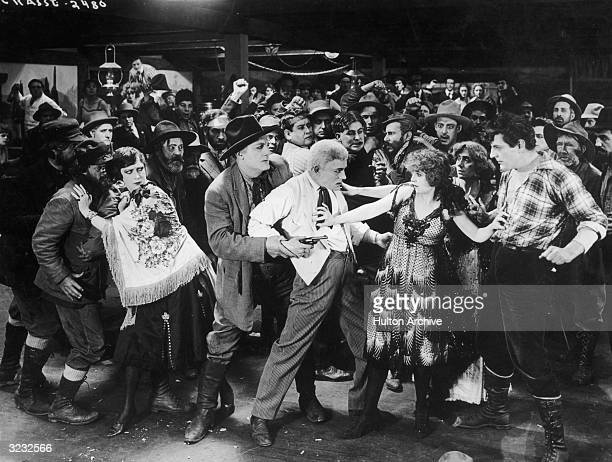 A scene from director Joseph De Grasse's silent film 'Pay Me' Lon Chayney points a revolver at a defiant William Stowell while Dorothy Philips tries...