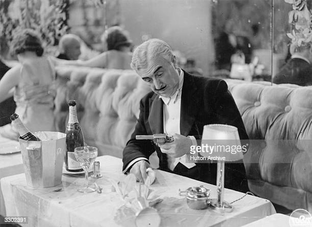 A scene from the film '14 Juillet' directed by Rene Clair An elderly man on a banquette seat in a restaurant stares at a revolver