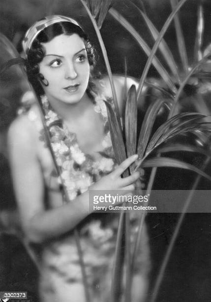A scene from the film 'Le Dernier Milliardaire' with Renee St Cyr peering through the shrubbery The film was directed by Rene Claire for Pathe Natan