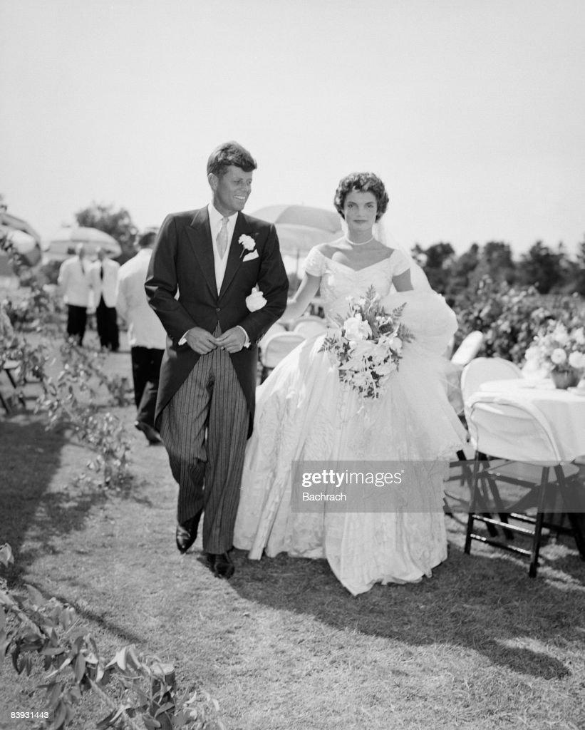 A scene from the Kennedy-Bouvier wedding. Groom John walks alongside his bride Jacqueline at an outdoor reception, 1953. Newport, Rhode Island.