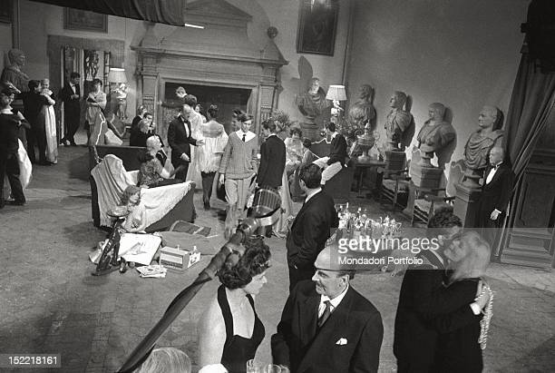 A scene from the movie 'La Dolce Vita' in the living room of the castle where actors take position among them Marcello Mastroianni while peeps out a...