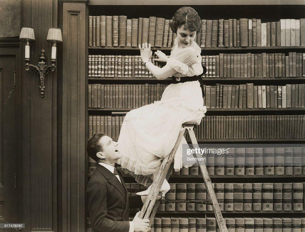 Man Shaking a Woman's Ladder : News Photo