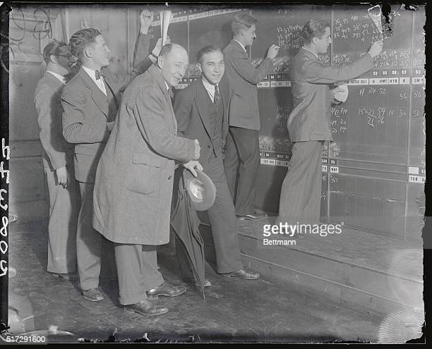Scene in stock broker's office with purchasers showing their joy as steadily increasing values are chalked up on quotation board