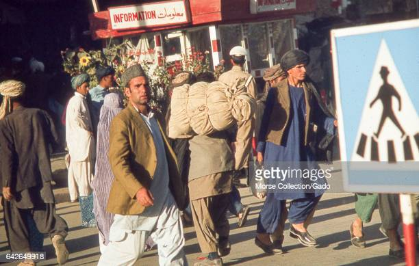 Scene of a crowded street in Kabul Afghanistan as men in traditional dress walk by an information booth on the sidewalk November 1975 In the extreme...