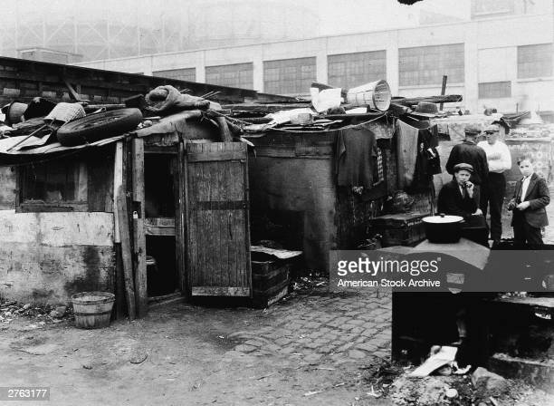 Scene of a group of men and a boy standing outside a shack in a shantytown named 'Hooverville' during the Great Depression circa 1930s