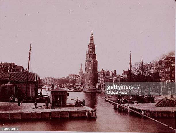 A scene of a tower along a canal in Amsterdam the Netherlands ca 1880s1890s