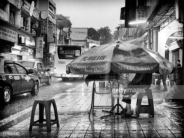 CONTENT] A scene of a very heavy pouring rain besieging the streets of Petaling with a helpless newspaper vendor forced to seek refuge under his...