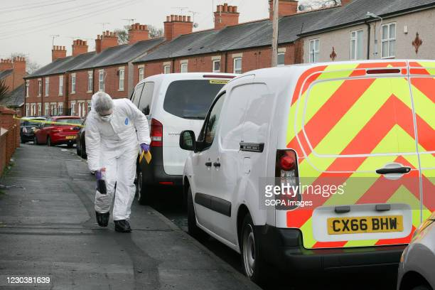 Scene of Crime Officer collects and photographs evidence at a suspected murder scene in a quiet residential street on New Year's Day. A crime scene /...