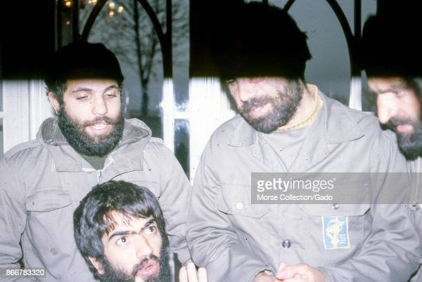 Scene of four bearded men wearing military uniforms engaged in discussion in a hotel in Iran March 1983 Extensive damage on original photo