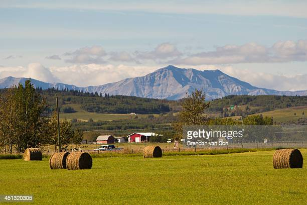 CONTENT] A scene of hay bales and mountains along the cowboy trail of Alberta Canada
