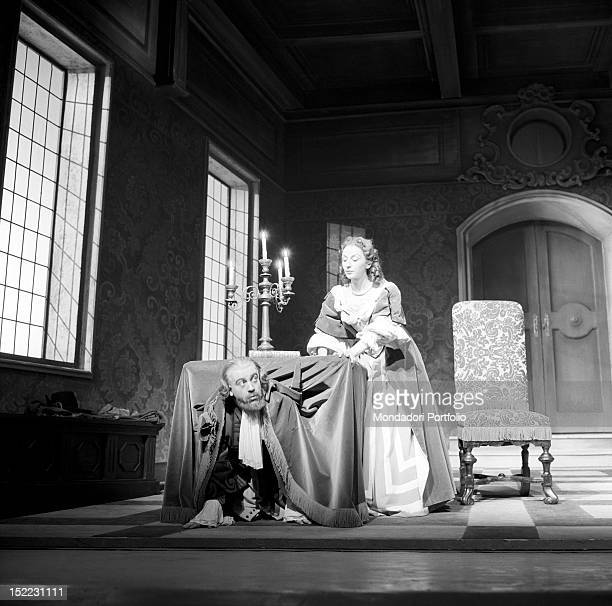 A scene of 'Tartuffe' by Molière the actor Glauco Mauri intepreting the role of Orgon has been hidden under a table by his wife Elmire interpreted by...