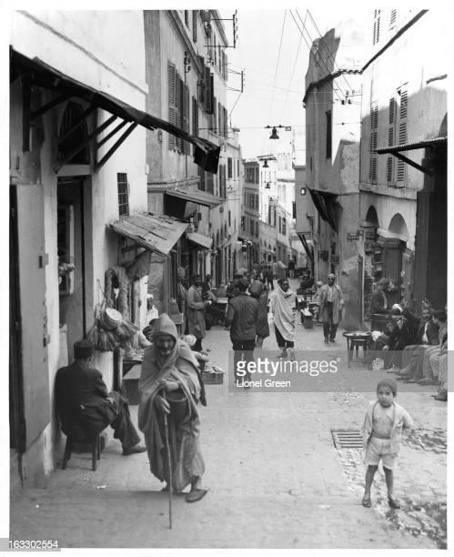 A scene on a narrow street with people sitting at tables and some walking as the buildings shade the street over them in Casbah Algiers 1955