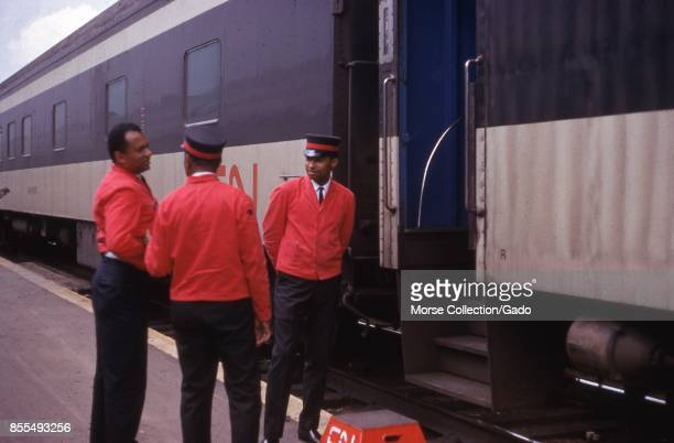 Scene on a station platform of three African American porters talking outside of a train car entrance July 1969 A footstool at the bottom of the...