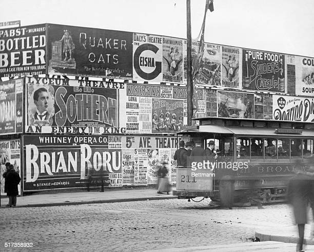 Scene on Broadway in New York City with large poster boards and passing streetcar Undated photograph