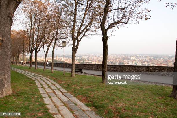 scene on old city wall promenade of citta alta in bergamo in autumn - bergamo alta foto e immagini stock