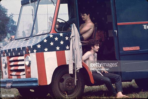 Scene showing two male festival attendees sitting shirtless in a van that has been painted with an American flag motif Woodstock NY 1969