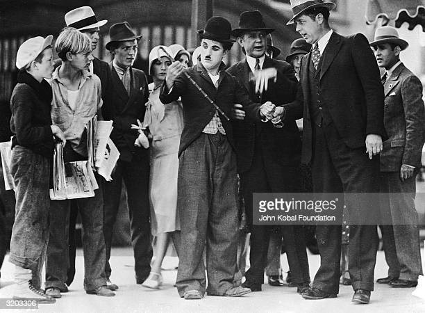 A scene that was cut from the film 'City Lights' starring Charlie Chaplin Robert Parrish is the first newsboy on left wearing the white newsboy style...