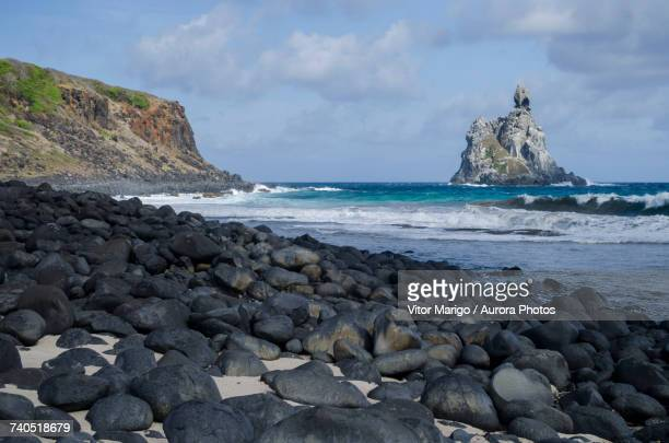 Scenery with pebbles at Atalaia Beach with rock formation in sea in distance