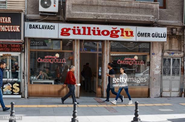 """Szenen aus dem Alltag in der Türkei. Menschen im Stadtzentrum von Gaziantep spazieren vor dem berühmten """"G ' ll? oglu Baklava""""-Shop"""