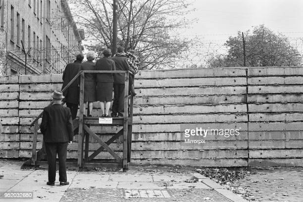 Scenes in Berlin three years after work began on the construction of the Berlin Wall separating East from West West Berlin citizens peers over the...