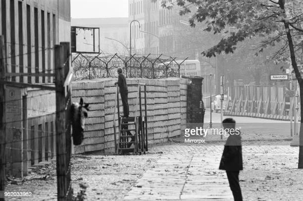 Scenes in Berlin three years after work began on the construction of the Berlin Wall separating East from West A West Berlin citizen peers over the...