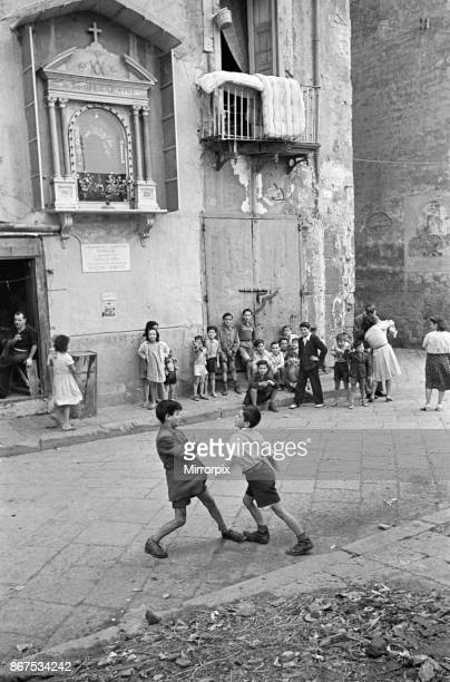 Scenes in Naples, southern Italy showing young boys entertaining themselves and other local children with a fight outside a church, circa 1955.
