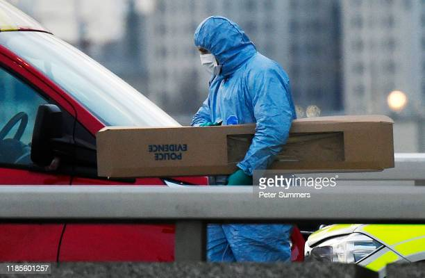 A scenes of crime officer removes a large piece of evidence from the scene of yesterday's London Bridge stabbing attack on November 30 2019 in London...